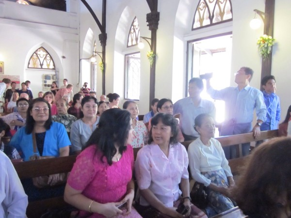 A packed church on Oct. 4, 2014. Tina Minus talks to Winsome Vertannes in the centre. Winsome's mother waits for the service to start.