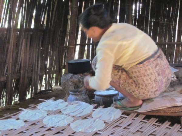 Woman making rice crackers over a charcoal fire. She makes up to 400 per day and sells them in the market.
